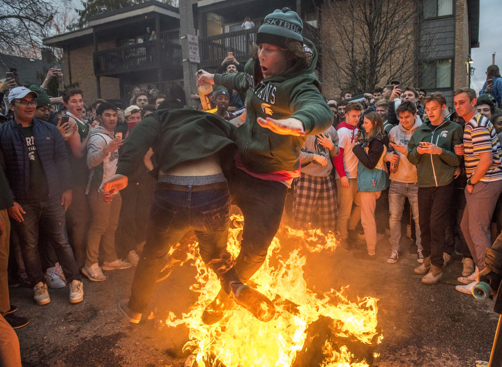 Nathan, 21, collides with a fellow Michigan State University student while jumping over a burning couch in celebration of MSU's victory over Duke in the NCAA Men's Division I Basketball Elite Eight at Cedar Village Apartments on March 31, 2019. Michigan State University students have a tradition to gather at Cedar Village, an apartment complex that borders MSU's campus and burn couches after notable wins from their sports teams.